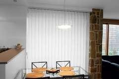 Белые вертикальные жалюзи в кухню студию