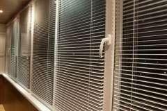Горизонтальные жалюзи на окнах пластикового балкона. Вид сбоку