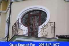 Балконный блок с овальной формой окон и тёмной коричневой ламинацией пластикового профиля